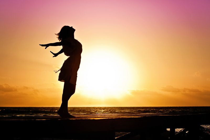 Girl standing on the beach at sunset her arms wide free from depression.