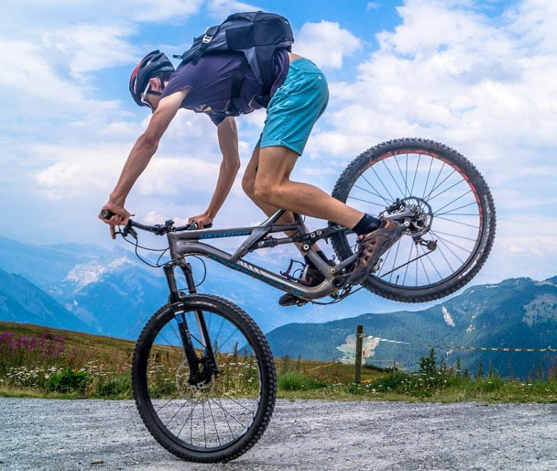Man balancing on the front wheel of his mountainbike while exercising.