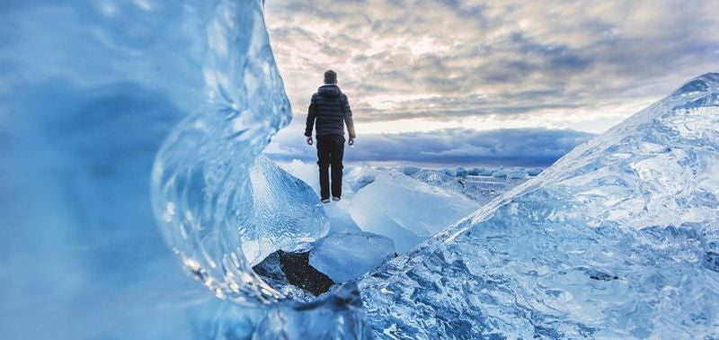 Man standing in on blue ice in the arctic