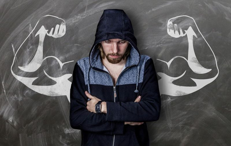 Man standing against a wall, arms folded.  The picture in the background is of strength.