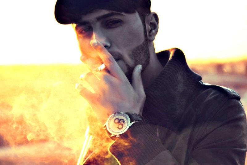 Young man standing smoking with the sunrising behind him.