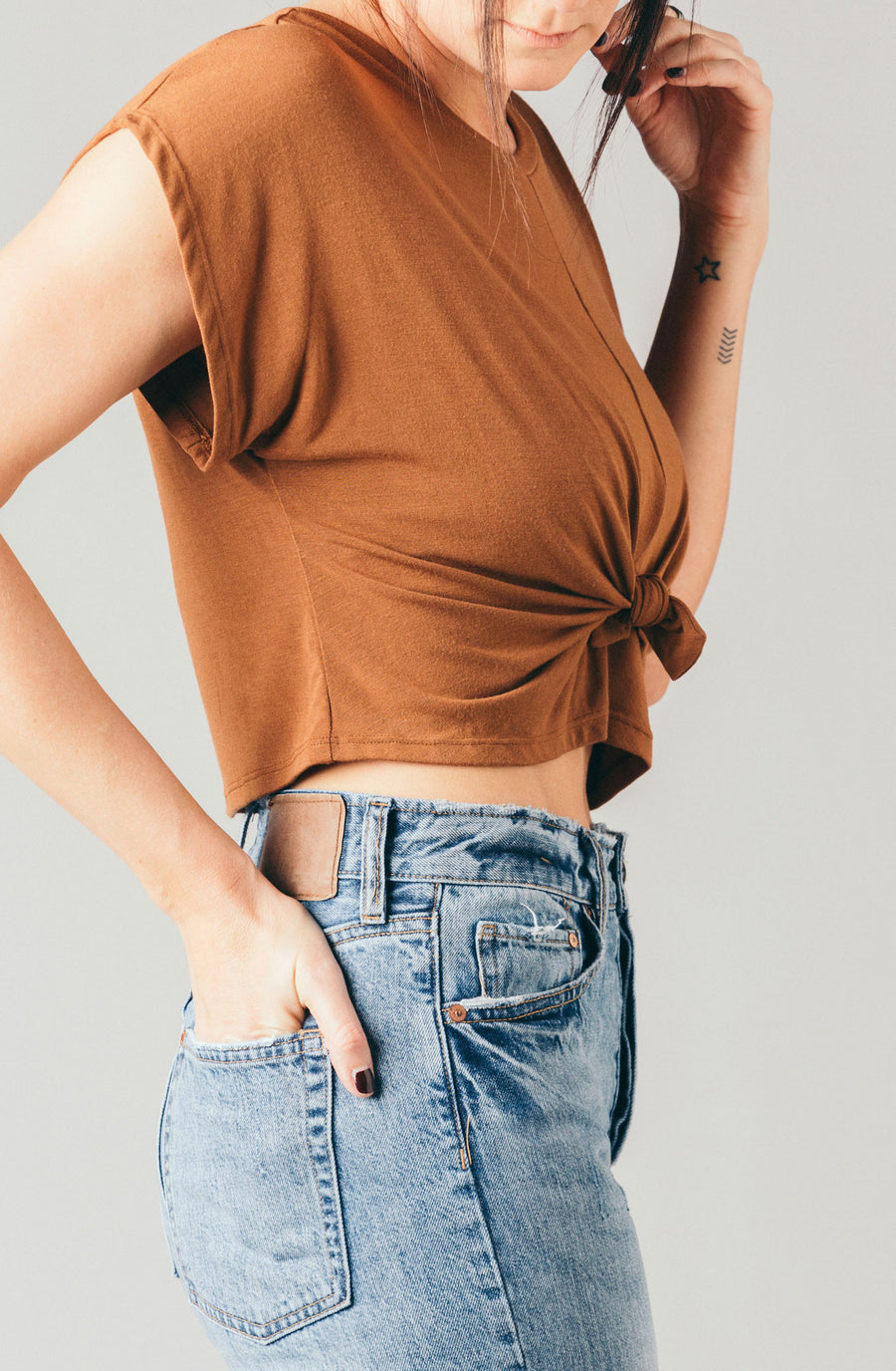 Corinne Collection rust brown short sleeve loose cropped tee with knotted front and cap sleeve.