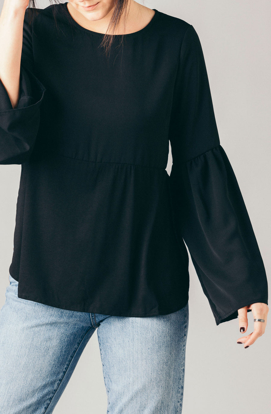 The Coverii black multi fabric jersey flowy blouse with long bell sleeves and double layer.
