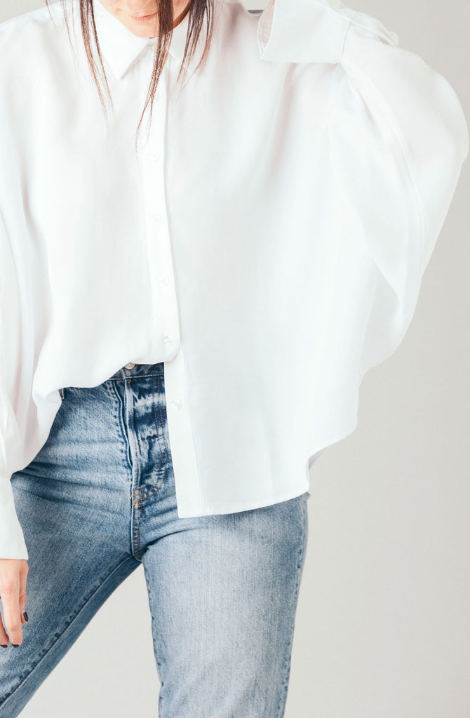 The Coverii white loose boyfriend collared boxy blouse with batwing dolman sleeves and ruffle bell cuff.