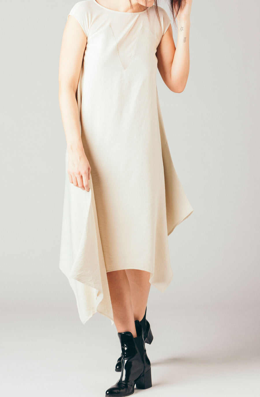 The Coverii ivory, cream linen blend dress with sheer shoulder v-neck, uneven sharkbite hem and backless mesh top.