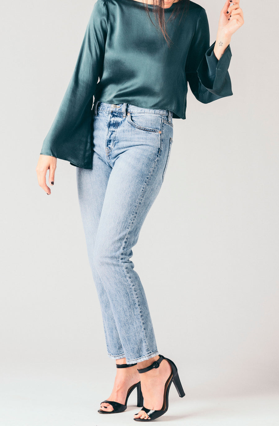 The Coverii emerald green silk long sleeve cropped blouse with bell sleeves.