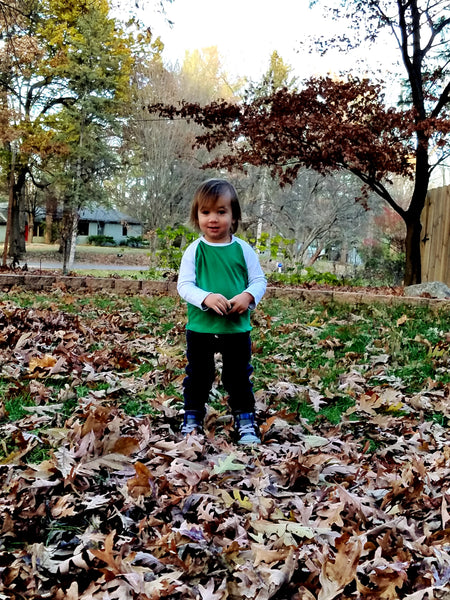 little boy wearing a green and white raglan-sleeve baseball tee in a fall scene with fallen leaves