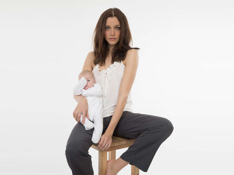 Pretty seated young mum wearing Cucumber Clothing ruffle breast feeding friendly ruffle top in cream with drawstring bottoms holding small baby.