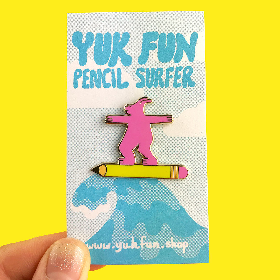 Cute pink pencil surfer dude enamel pin by YUK FUN