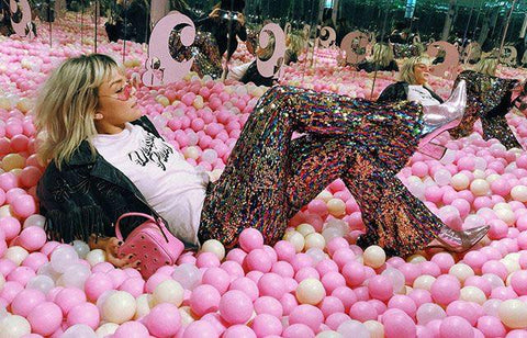 Glitzegal blogger influencer in pink ball pit wearing Sparklebutt rainbow sequin flares | Sparklebutt Festival costumes