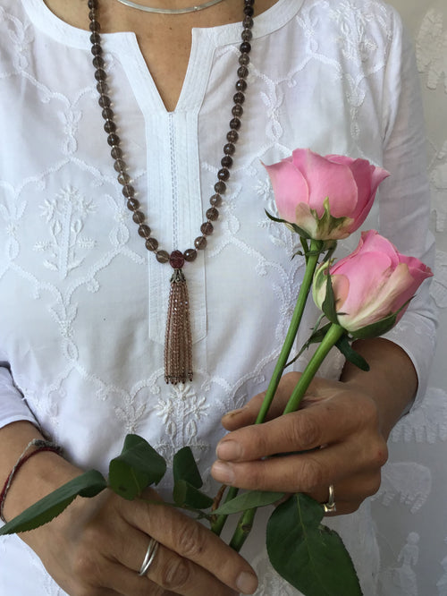 The Blissful Being Mala in celestial smokey quartz has an exquisitely beaded crystal tassel and separators. Necklace view.