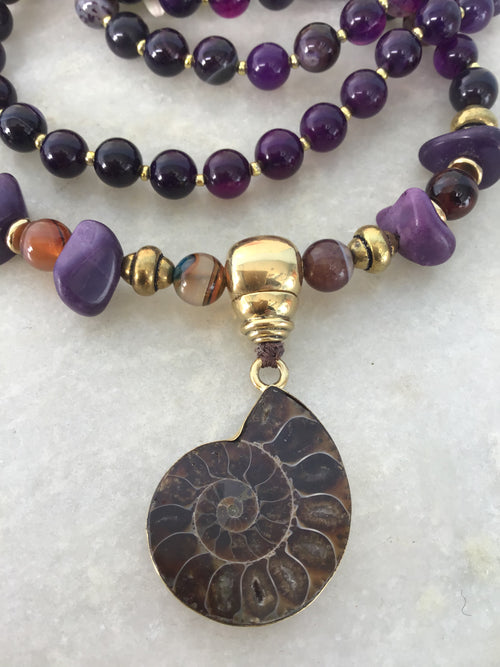Divya Devi Mala in violet twirl Onyx/Agate and stunning brass nautilus. Closeup view of nautilus.