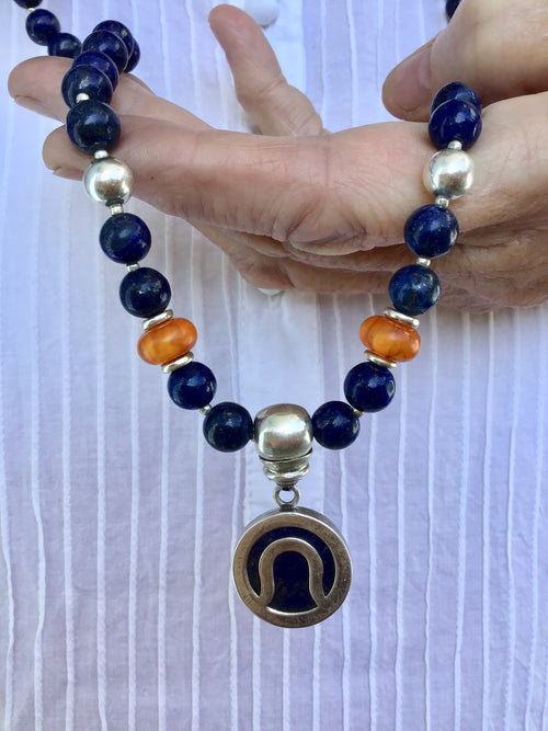 I Am I Celebration Mala is tied in 8mm lapis lazuli, and has a lapis and 925 silver pendant, and silver and amber accents. Hand view.