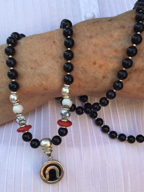 Immortal Am I Celebration Mala in obsidian black onyx with howlite and 925 silver. Hand view.
