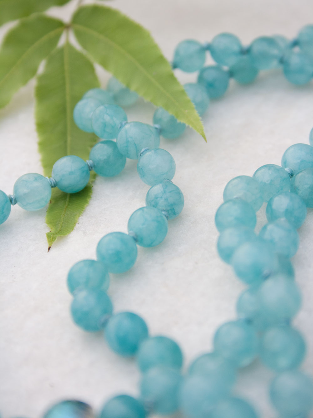 Babylonian Flower Mala in aqua blue aventurine has crystal Guru and 925 silver flower of life. Alternate partial view.