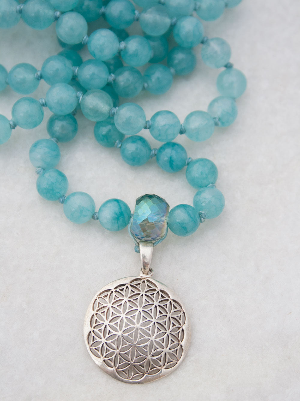 Babylonian Flower Mala in aqua blue aventurine has crystal Guru and 925 silver flower of life. Partial view.