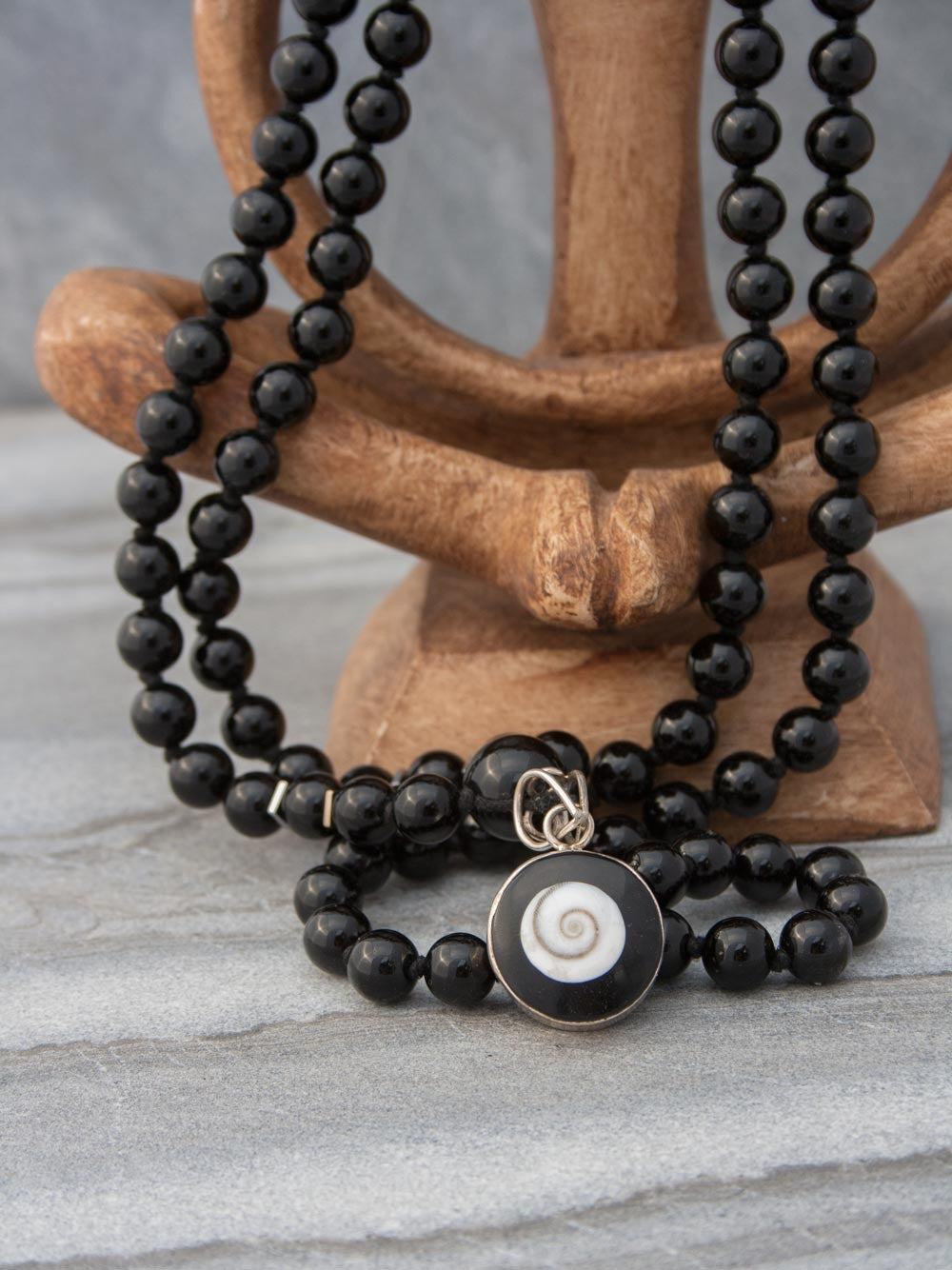 Absolute Bliss Mala, in obsidian onyx, has an ivory shell,  black onyx & silver Shiv Eye pendant: view of Shiv Eye