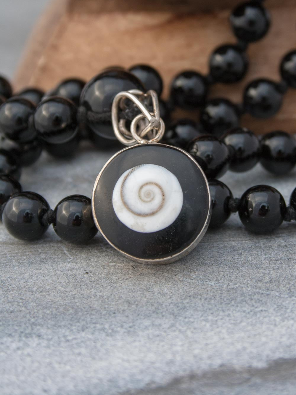 Absolute Bliss Mala, in obsidian onyx, has an ivory shell,  black onyx & silver Shiv Eye pendant: closeup view of Shiv Eye
