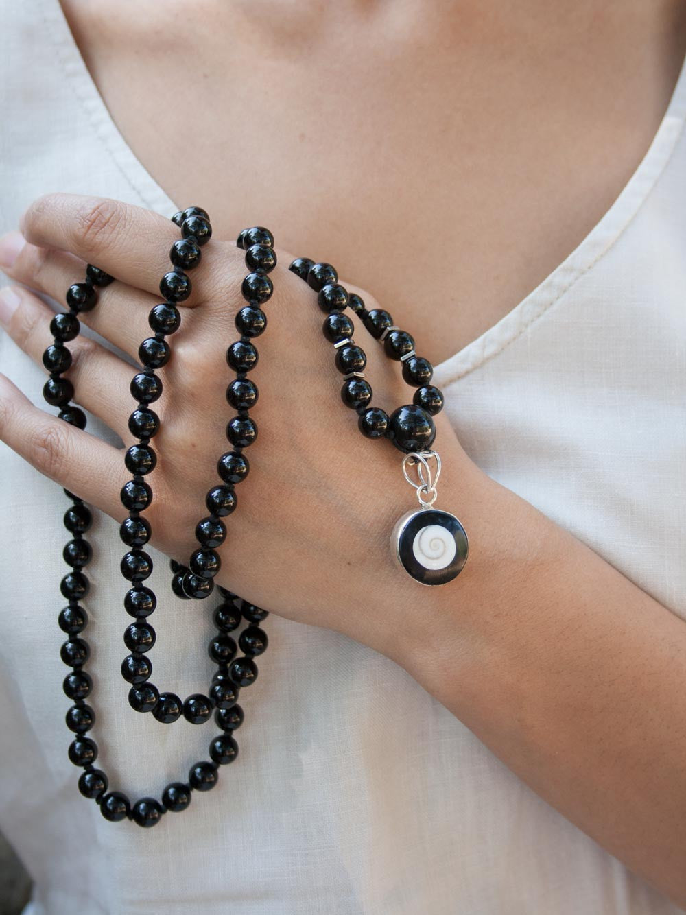 Absolute Bliss Mala, in obsidian onyx, has an ivory shell,  black onyx & silver Shiv Eye pendant: hand view