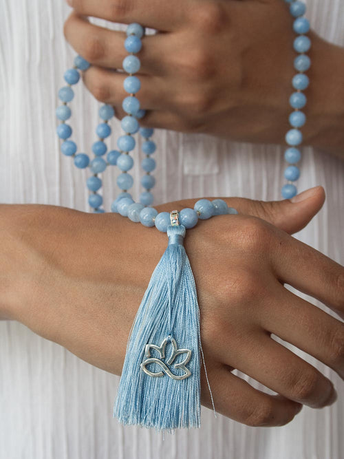 Serenity Mala, in heavenly blue aventurine, with Swarovski crystal Guru and 925 silver lotus. Hand view.