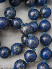 Unstruck Om Mala, for meditation and awareness, in 12mm Lapis Lazuli, has a stunning coral Guru bead and silver Mantra talisman: bead view.