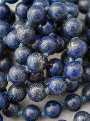 Unstruck Om Mala, for meditation and awareness, in 12mm Lapis Lazuli, has a stunning coral Guru bead and silver Mantra talisman: bead view alternate.