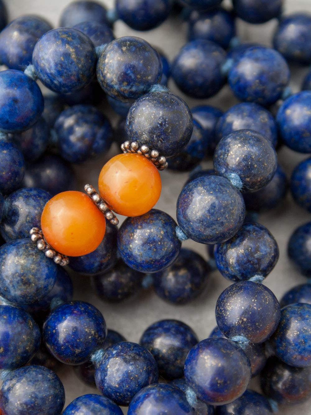 Resounding Om Mala is hand-knotted in 10mm lapis lazuli, with amber accents, handmade 925 silver Om Guru, and vibrant sari silk tassel: bead and accents alternate view.