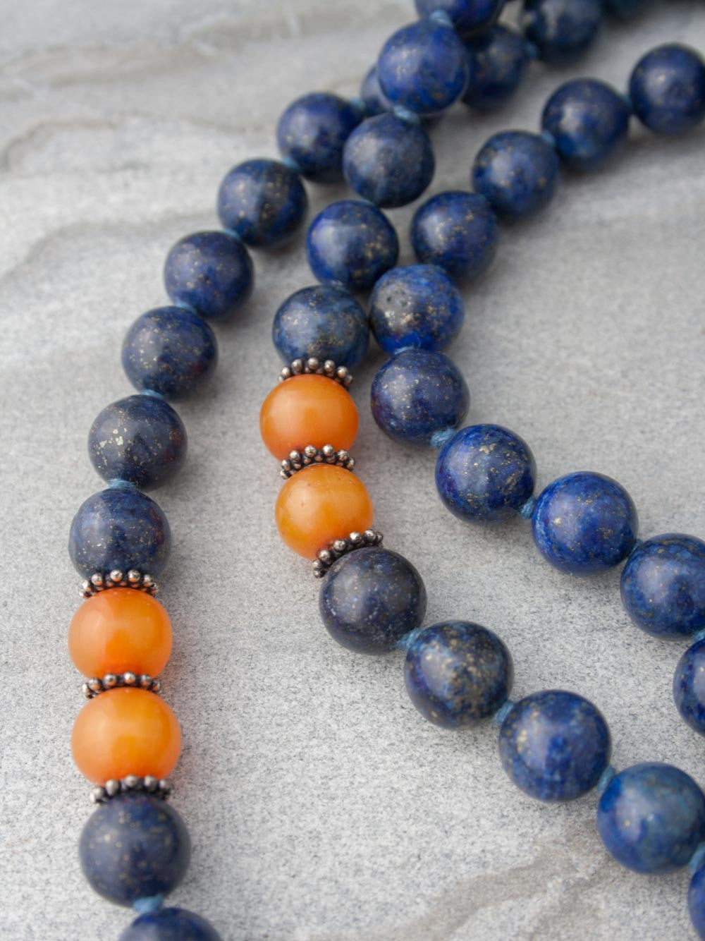 Resounding Om Mala is hand-knotted in 10mm lapis lazuli, with amber accents, handmade 925 silver Om Guru, and vibrant sari silk tassel: bead and accents view.