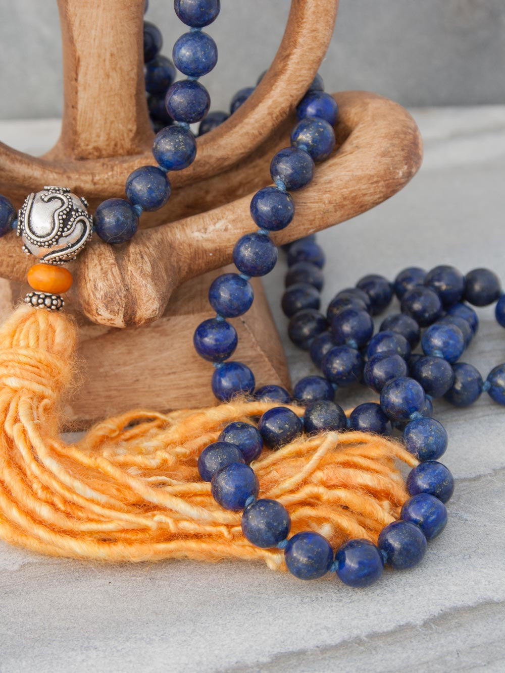 Resounding Om Mala is hand-knotted in 10mm lapis lazuli, with amber accents, handmade 925 silver Om Guru, and vibrant sari silk tassel: partial view.