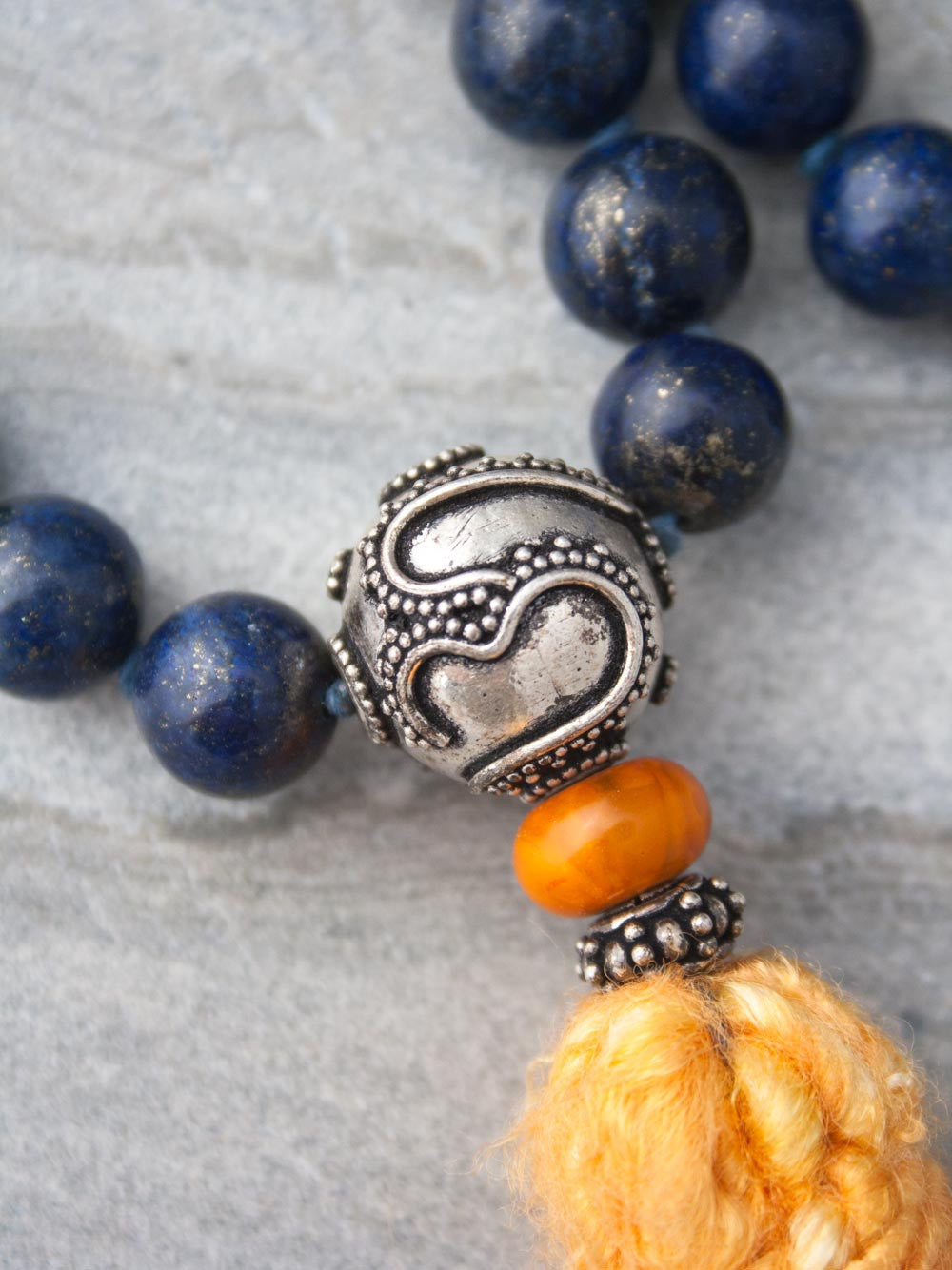 Resounding Om Mala is hand-knotted in 10mm lapis lazuli, with amber accents, handmade 925 silver Om Guru, and vibrant sari silk tassel: view of Guru bead.