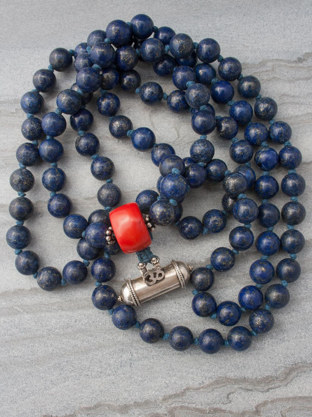 Unstruck Om Mala, for meditation and awareness, in 12mm Lapis Lazuli, has a stunning coral Guru bead and silver Mantra talisman: full view.