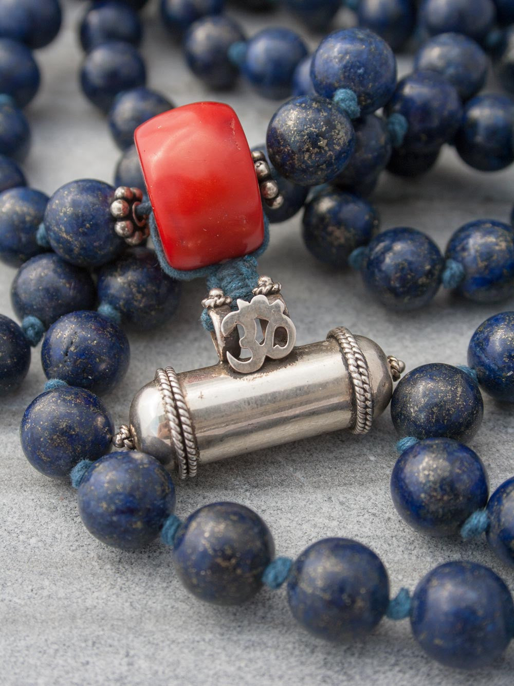 Unstruck Om Mala, for meditation and awareness, in 12mm Lapis Lazuli, has a stunning coral Guru bead and silver Mantra talisman: Guru bead and talisman view.