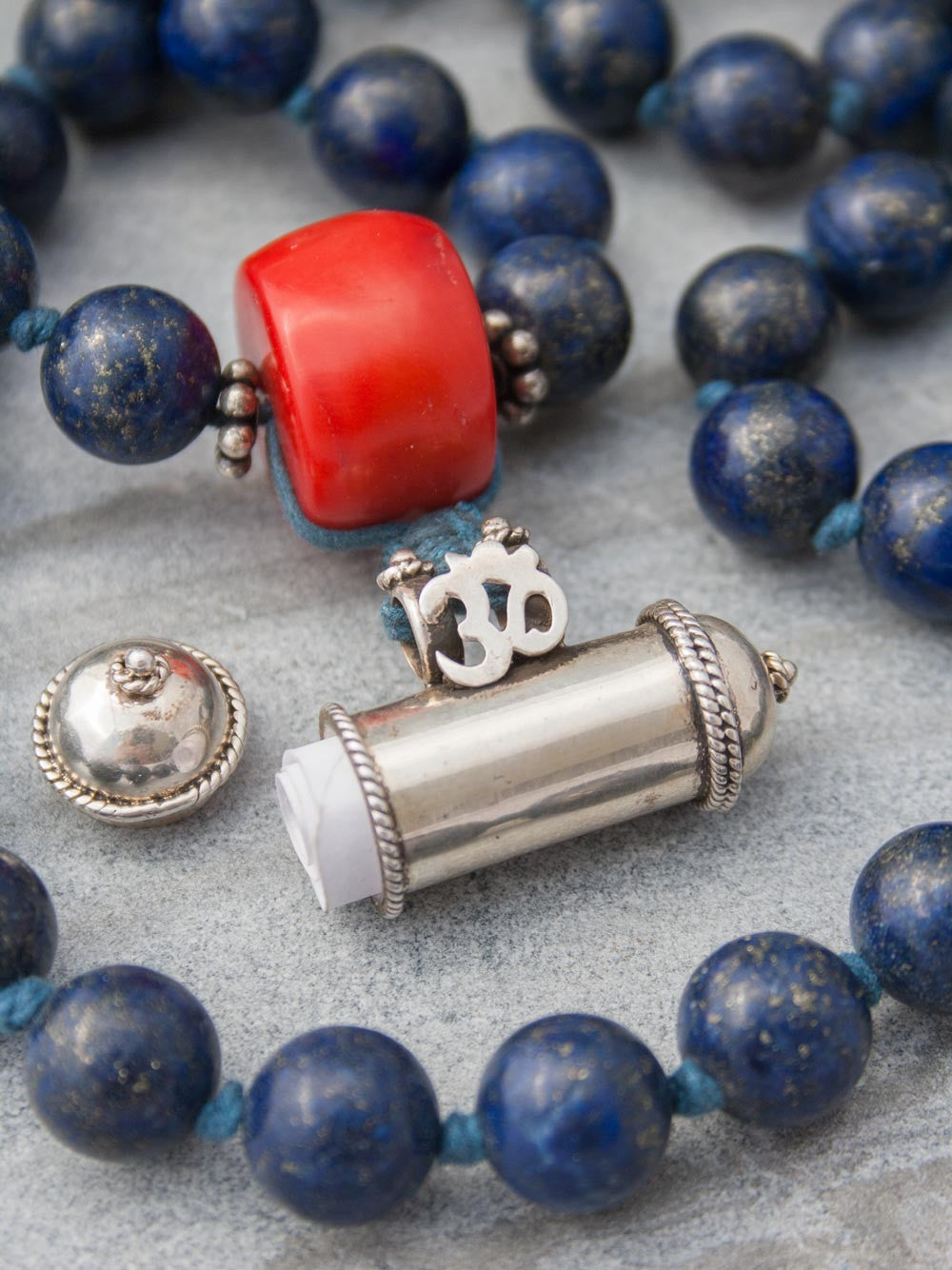 Unstruck Om Mala, for meditation and awareness, in 12mm Lapis Lazuli, has a stunning coral Guru bead and silver Mantra talisman: open talisman view.