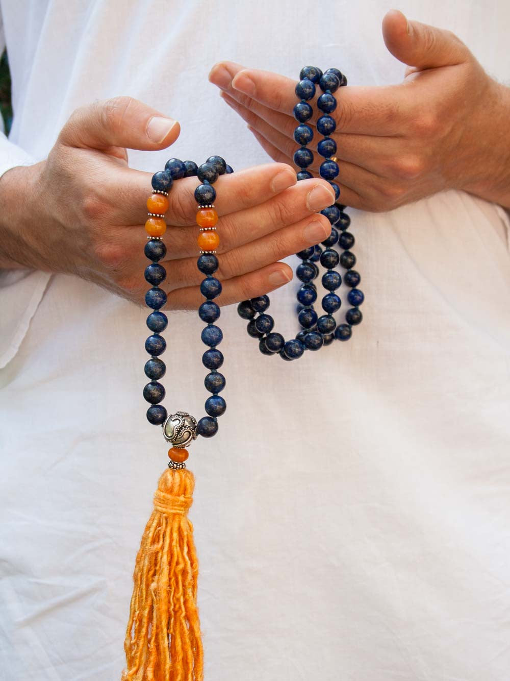 Resounding Om Mala is hand-knotted in 10mm lapis lazuli, with amber accents, handmade 925 silver Om Guru, and vibrant sari silk tassel: hand view alternate.