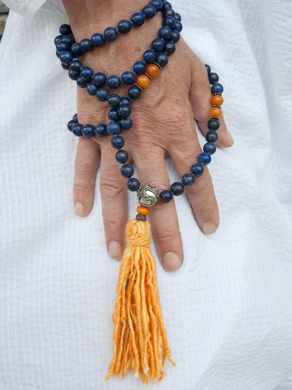 Resounding Om Mala is hand-knotted in 10mm lapis lazuli, with amber accents, handmade 925 silver Om Guru, and vibrant sari silk tassel: hand view.