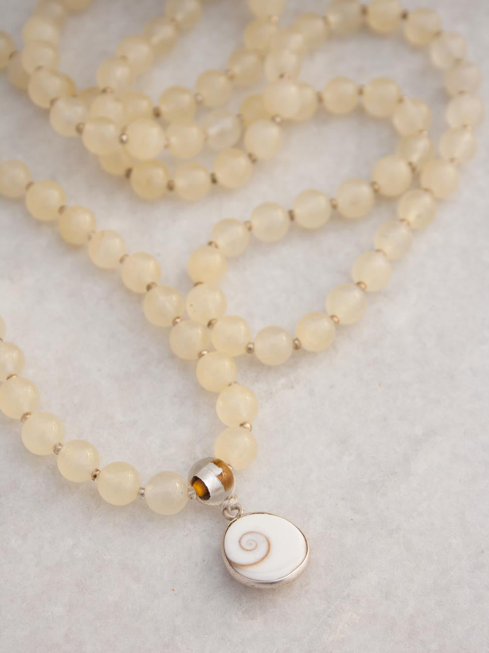 Infinite Bliss Mala, in 8mm citrine yellow aventurine, has a glass/silver foil Guru bead & shell/silver Shiv Eye pendant: partial view