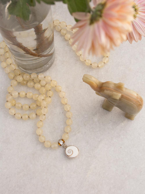 Infinite Bliss Mala, in 8mm citrine yellow aventurine, has a glass/silver foil Guru bead & shell/silver Shiv Eye pendant: view from above