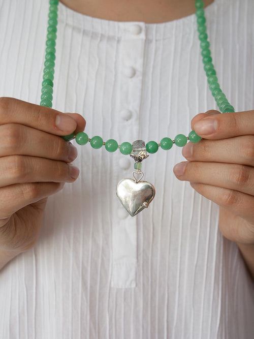 Eternal Heart Mala in goddess green aventurine, has a handcrafted 925silver heart locket and crystal Guru setting. Hand view.