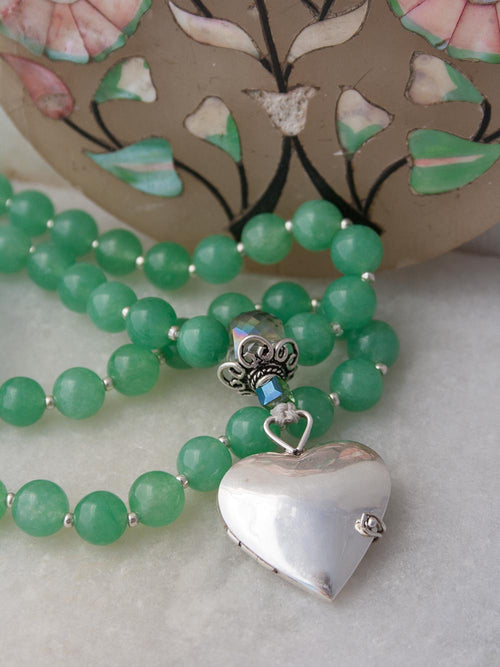Eternal Heart Mala in goddess green aventurine, has a handcrafted 925silver heart locket and crystal Guru setting. Partial view.