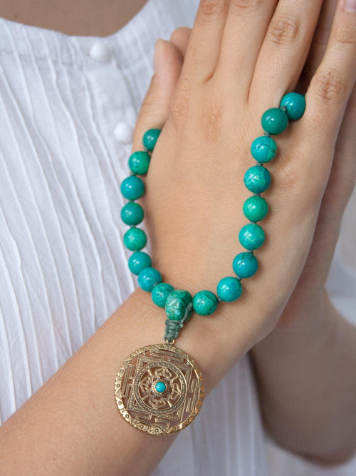 Infinity Hand-held Mala, in distinctive 10mm turquoise, with brass Mandala: hand view
