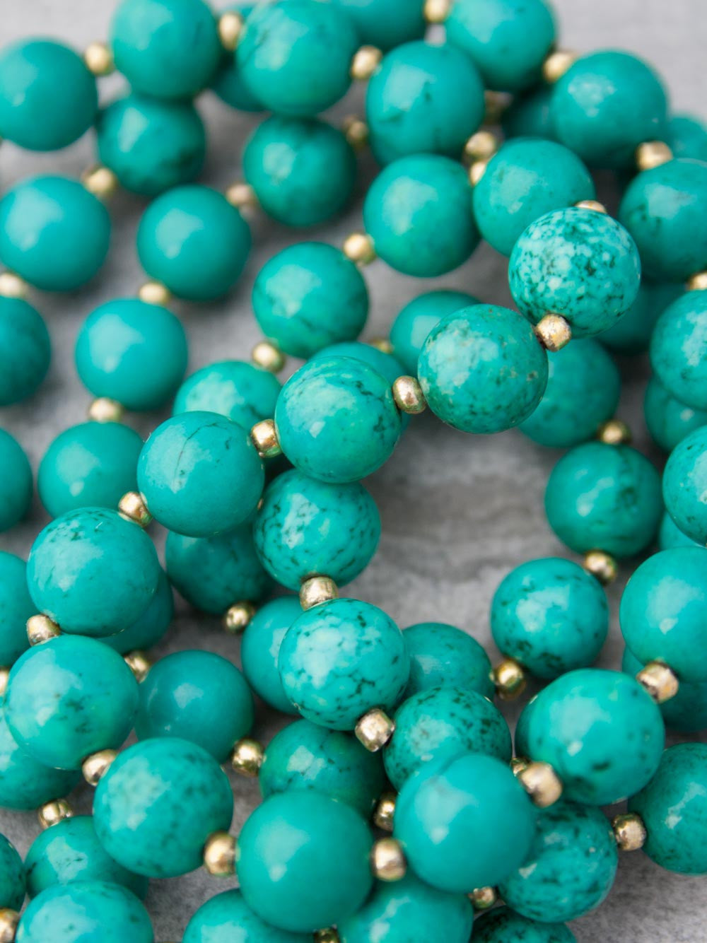 Infinity Celebration Mala in distinctive 8mm turquoise, with brass Mandala: bead view