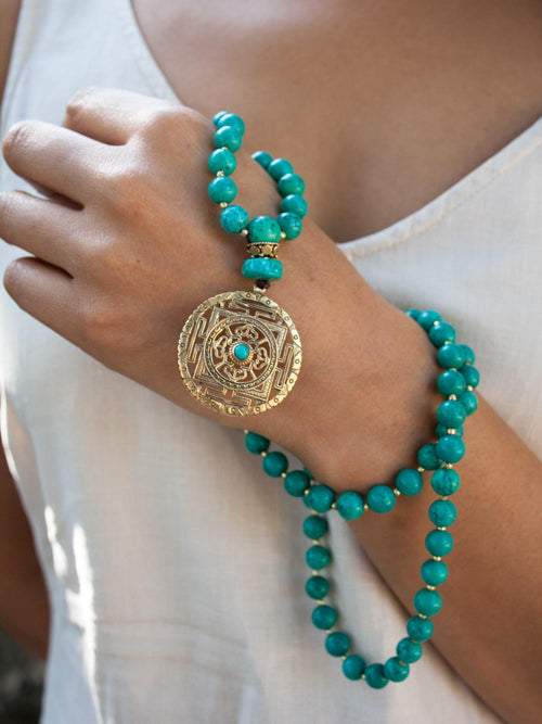Infinity Celebration Mala in distinctive 8mm turquoise, with brass Mandala: hand view