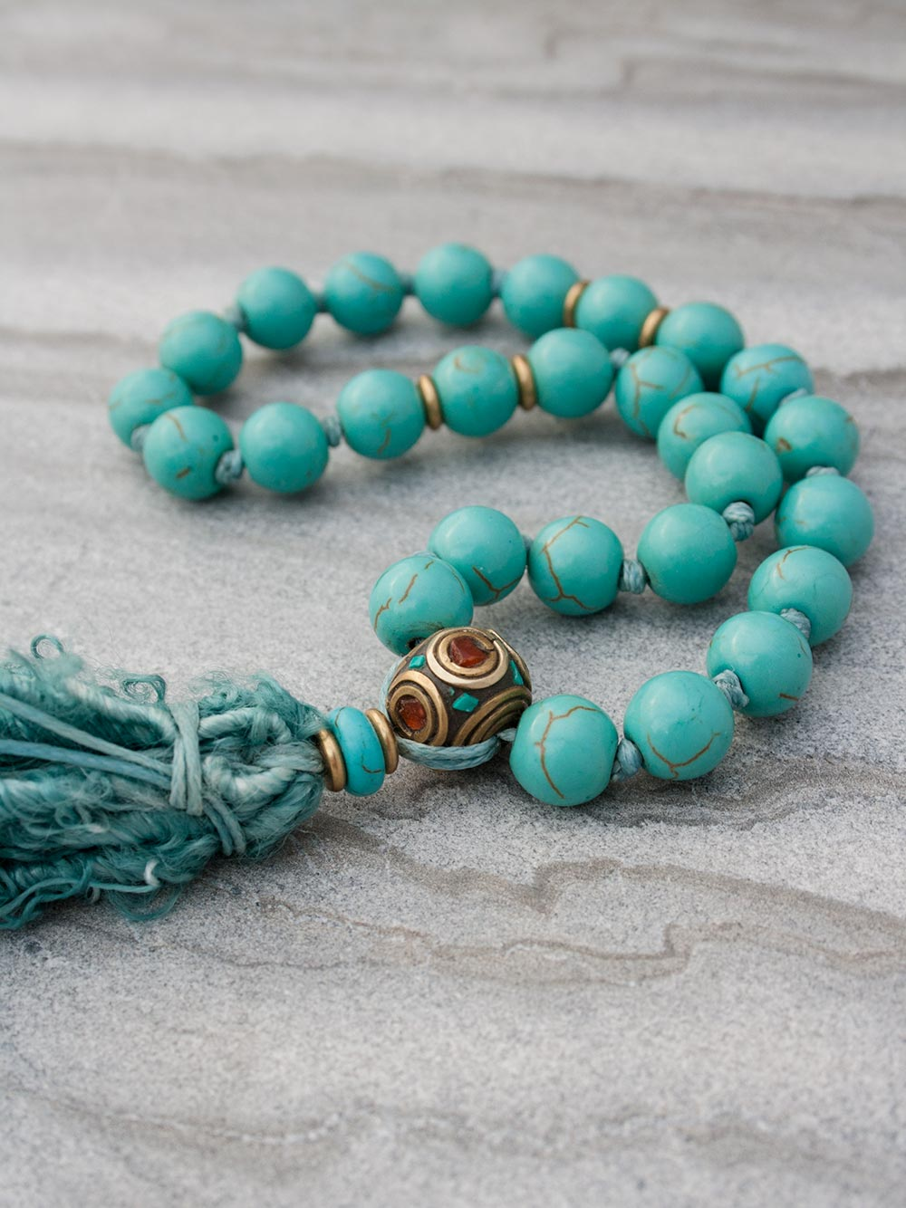 Caprice Hand-Held Mala: 27 beads in 10mm capriccio aqua howlite, with howlite and brass/coral/turquoise Guru setting and sari silk tassel. Full view alternate.