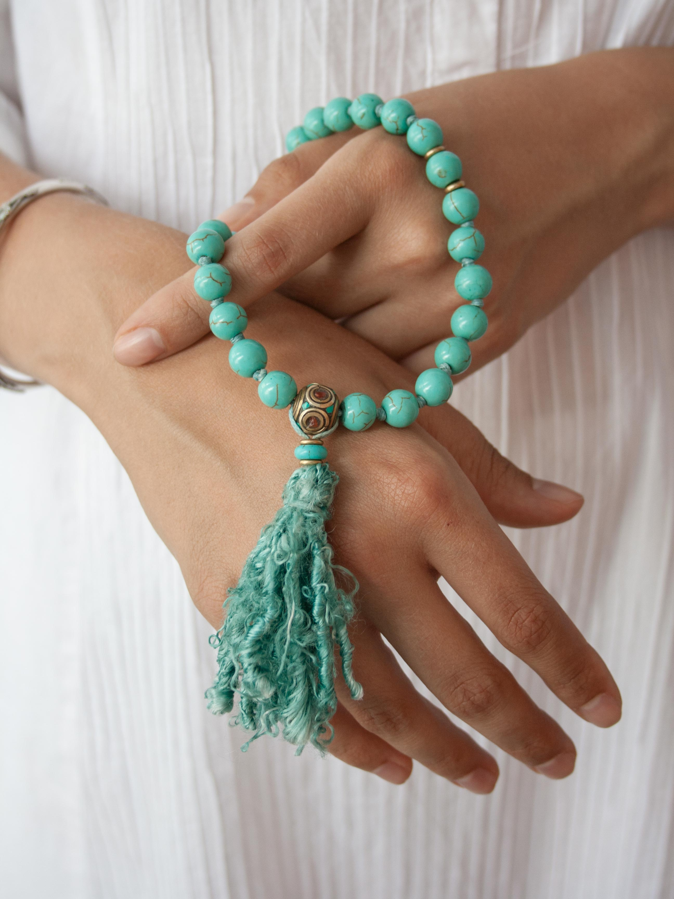 Caprice Hand-Held Mala: 27 beads in 10mm capriccio aqua howlite, with howlite and brass/coral/turquoise Guru setting and sari silk tassel. Hand view.