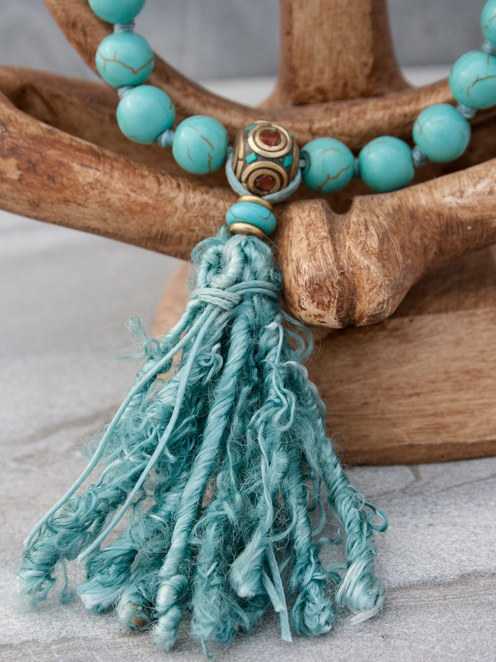 Caprice Hand-Held Mala: 27 beads in 10mm capriccio aqua howlite, with howlite and brass/coral/turquoise Guru setting and sari silk tassel. View of Guru setting.