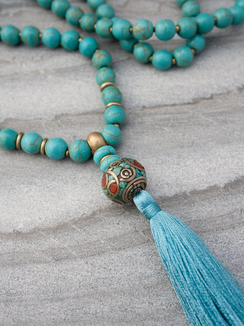 Caprice Celebration Mala, in 8mm capriccio aqua howlite, has a whimsical Guru setting in howlite, brass/coral/silver, and 'silk' tassel. Alternate view of Guru setting.