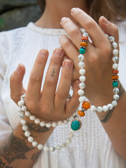 Victory Ganesh Mala is glorious & victorious in hand-knotted alabaster howlite, amber, coral & turquoise: hand view.