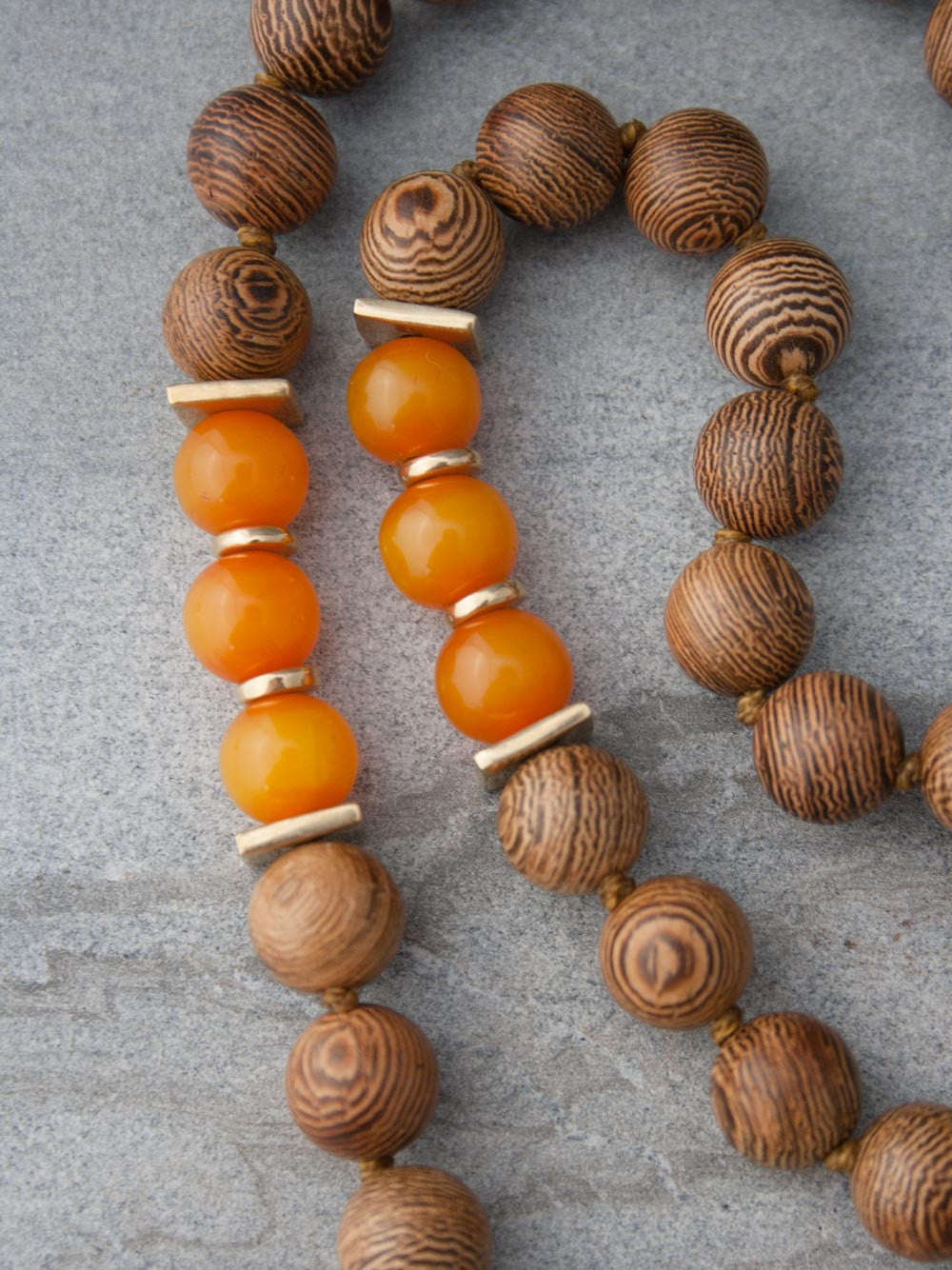 Eternal Existence Mala is made of 10mm wengewood beads, & has amber accents & a sari silk tassel: bead & accents view
