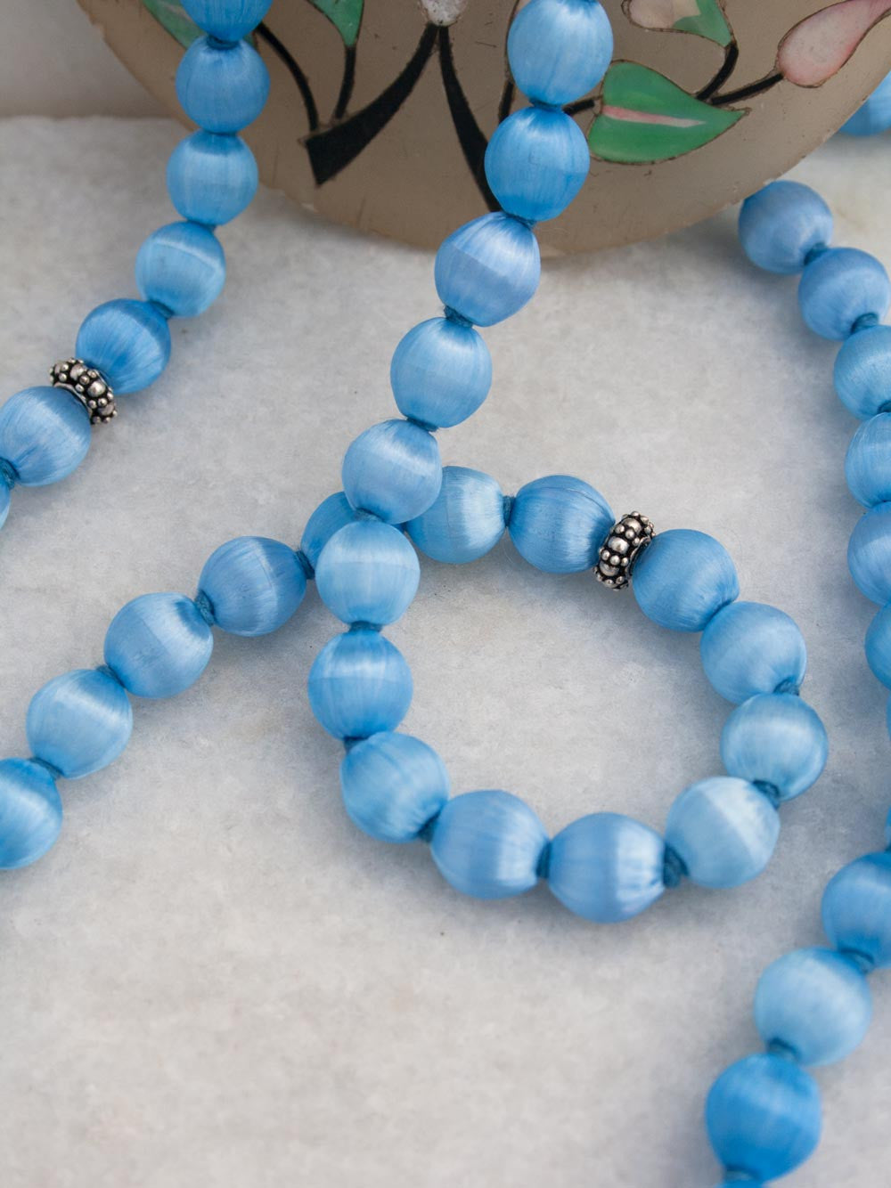 Celestial Blue Silk Mala, hand-knotted, has a silver Guru bead & silk tassel: beads & accents view