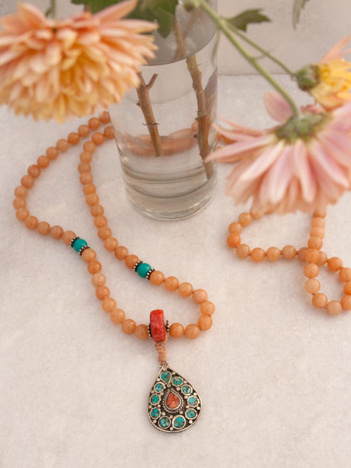 The Rani Mala, in Tuscan peach Aventurine, has a striking Coral Guru and exotic teardrop pendant: full view.